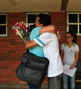 Professora Eva Campos recebe as flores dos alunos Judivan e Alice.